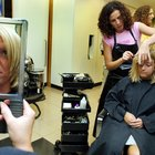 Close-up of a female hairdresser dyeing a mid adult woman's hair