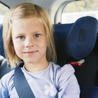 Three girls (6-8 years) sitting on rear seat of car during road trip
