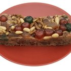 Fresh baked fruitcake for Christmas on plate and spruce branches on boards