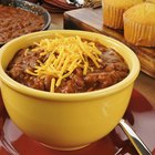 Beef chili with beans and cheese topping in a bowl on a table