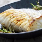 Grilled fish with lemon in pan , horizontal top view closeup