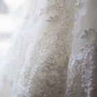 Wedding dress and veil on armchair in clothing store