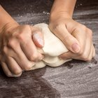 Woman's hands kneading dough in a kitchen
