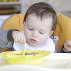 happy baby child eats itself with a spoon