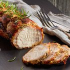 Pork chop in a serving dish with rosemary and tomatoes
