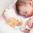 Baby girl yawning in a white round crib