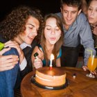 Woman blowing out candles at party