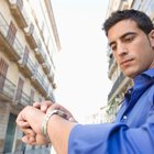 Mid adult man standing at street, looking at watch
