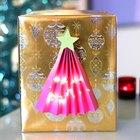 Envoltorio de regalos con un árbol de Navidad iluminado