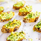 Crostinis de aguacate con miel, pistachos y semillas de sésamo negro