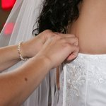 Have someone assist you in pinning the bra to the bodice of your wedding dress.