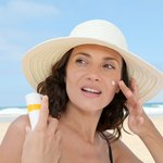 Woman applying sunscreen to the face