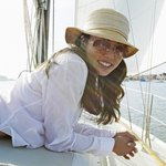 A straw hat protecting a woman on a boat deck from the sun.