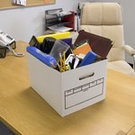 Box with office belongings on desk, symbol of unemployment.