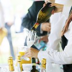 A server pours champagne at an event.