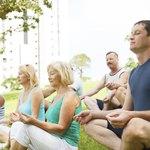 Yoga class meditating on lawn