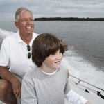 Grandfather and grandson riding in boat