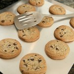 Freshly baked chocolate chip cookies on a baking sheet.