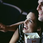 A young couple is watching a movie in a theater.