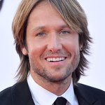 Singer Keith Urban uses long, feathered layers parted down the middle to make his large forehead look more proportionate.