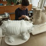 An artist makes a porcelain statue of a rhinoceros.