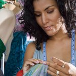 Image of a woman hand crafting and designing a dress on a mannequin.