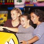 Teenage girls playing arcade game