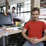 A designer sits at a desk in a modern office.