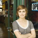 employee standing in front of open store