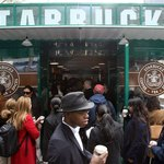 Customers gather outside a Starbucks store in Bryant Park in New York City