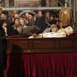 Mourners view the deceased in an open casket.