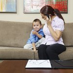 A woman talks on the phone while sitting on a sofa with her young son at home.