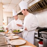A chef works in a hot, crowded kitchen.