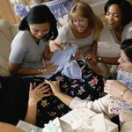 Women touching woman's stomach at baby shower.