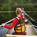 Father and daughter rowing in canoe on lake