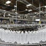 Factory line of water bottles on conveyor belt.