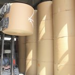 Large spools of paper in manufacturing plant