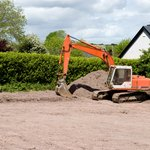 A bulldozer begins the construction process on an empty lot.