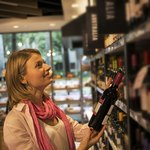 A woman selecting a bottle of wine in a shop.
