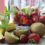A blender filled with strawberries and kiwi fruit.
