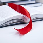 A red ribbon book mark in an open book.