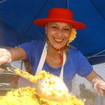 Spanish cook prepares paella at a farmer market stall