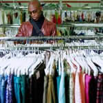 A man shops for clothing in a consignment shop.