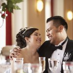 A happy bride and groom sit at a table at their wedding reception.