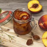 Small jar of nectarine syrup, surrounded by several necartines.