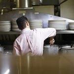 Commis chef stirring pots