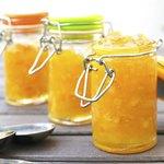 Three jars of orange chutney.