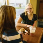 Two women sit at a checkerboard table in a coffeehouse.