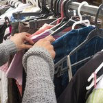 Woman looks through clothes at swap meet