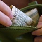 woman placing cash in her wallet